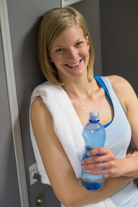 Sweaty woman with bottle and towel in locker room at gym