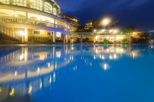 Swimming pool at a tropical resort illuminated at night