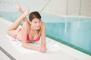 Swimming pool - beautiful woman relax listen to music with ear buds