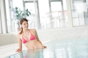 Swimming pool - beautiful woman wearing bikini in pool