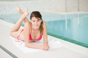 Swimming pool - happy woman relax listen to music with ear buds