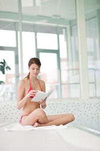 Swimming pool - woman relax with book sitting down