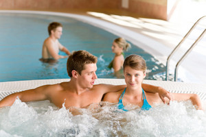 Swimming pool - young attractive couple relax in hot tub
