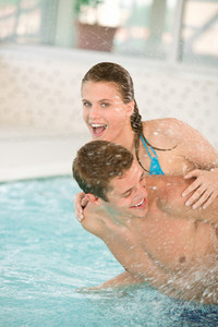 Swimming pool - young cheerful couple have fun under water stream