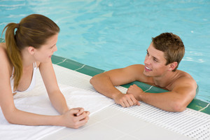 Swimming pool - young happy couple chat on poolside in luxury hotel