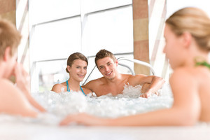 Swimming pool - young happy couple relax in hot tub