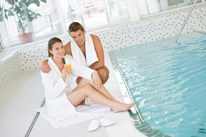 Swimming pool - young happy couple relax on poolside in luxury hotel