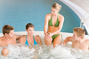 Swimming pool - young happy people relax in hot tub