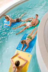 Swimming pool - young people have fun, lying on floating foam mattress