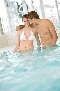 Swimming pool - young sportive couple have fun in water