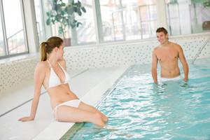 Swimming pool - young sportive couple relax,focus on woman in bikini
