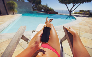 Tanned woman using smart phone by the poolside. Caucasian female model sunbathing on a deckchair and mobile phone.