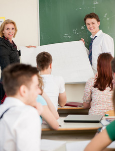 Teacher and a student holding a white banner in a classroom