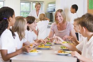 Teacher and schoolchildren enjoying their lunch in a school cafeteria