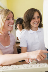 Teacher and schoolgirl studying in front of a school computer