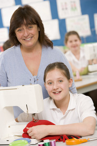 Teacher and schoolgirl using a sewing machine in sewing class
