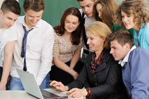 Teacher and students looking at laptop on a table