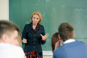 Teacher giving a lecture to her students in a classroom