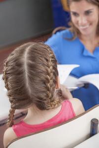 Teacher giving the exam for girl