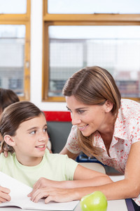 teacher helping a girl in the classroom
