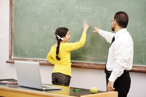 Teacher helping schoolgirl in front of board