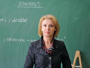 Teacher in the classroom on blackboard background.
