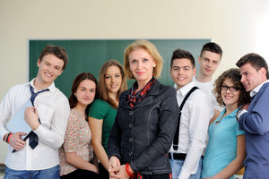 Teacher posing with her students in a classroom