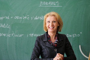 Teacher smiling in front of a chalkboard
