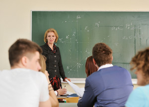 Teacher standing on a blackboard looking at her students