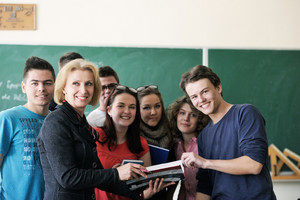 Teacher surrounded by her students in classroom holding a copybook