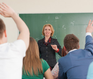 Teacher taking questions from her students in a classroom