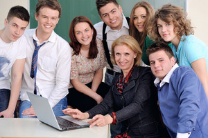 Teacher with laptop sitting behind a table posing with her happy students