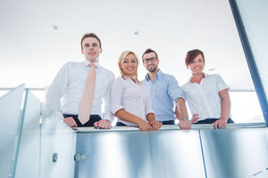 Team of businessmen leaning on a modern glass fence