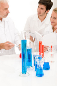 Team of scientists in laboratory - medical research,blue liquid in beakers