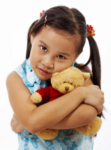 Teddy Bear Being Hugged By A Young Girl