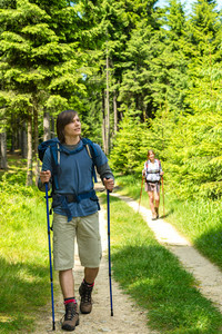 Teen hikers trekking in pine forest