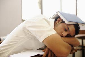 Teen student sleeping at classroom
