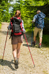 Teen tourists walking with trekking poles in woods