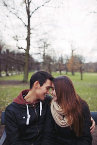 Teenage couple sitting on a bench and enjoying a day in the park. Beautiful young couple in park. Mixed race male and female model in love with copy space.