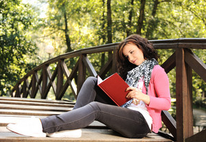 Teenager female reading in park