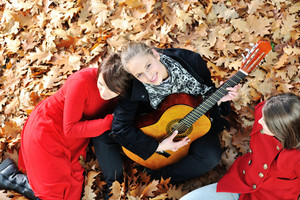 Teenagers friends playing the guitar at autumn park