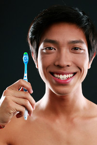 Teeth care young man with toothbrush
