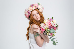 Tender charming young woman with long red hair in wreath posing with bouquet of flowers over white background