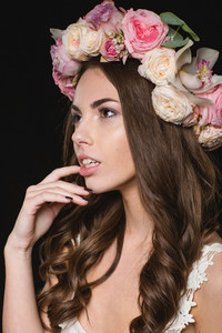 Tender pretty young female with beautiful curly long hair in rose wreath isolated over black background