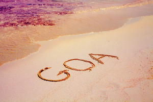 Text GOA on the sand on the beach