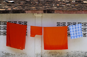 Thai Buddhist monks' robes hanging at a temple wall in Laos