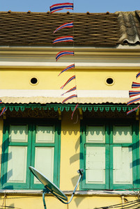 Thailand flag with wooden window on yellow house