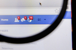 THAILAND - SEPTEMBER 2, 2014: Magnifying glass of Facebook page friend message feed on browser.