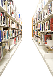The aisles in a public library with shelves full of books - isolated over white.