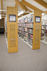 The aisles in a public library with shelves full of books.